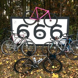 Multiple fixed gear bikes standing around a big sign with 666 written on it